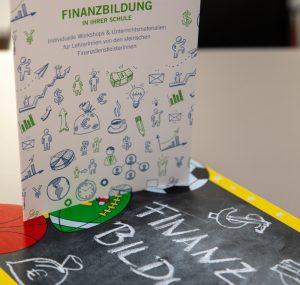 Folder zur Finanzbildung und Schultafel