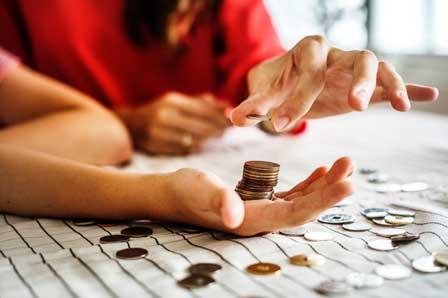 2 Personen zählen Münzen die auf dem Tisch liegen