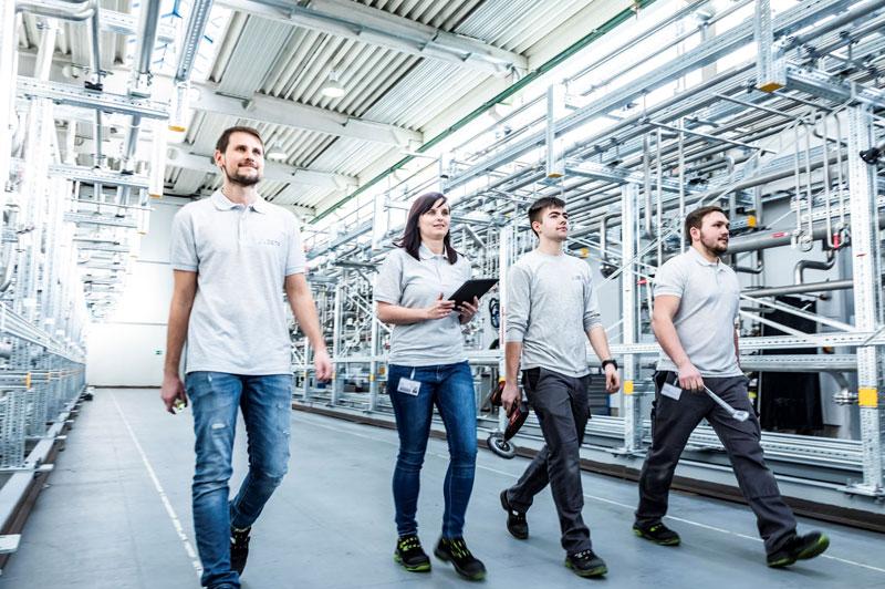 4 MitarbeiterInnen gehen durch eine Fabrikshalle